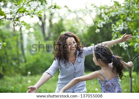 mother and daughter in the spring garden - stock photo