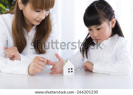 mother and daughter is looking at miniature house - stock photo