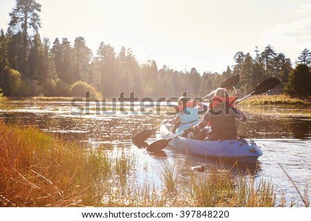 Mother and daughter kayaking on lake, back view - stock photo