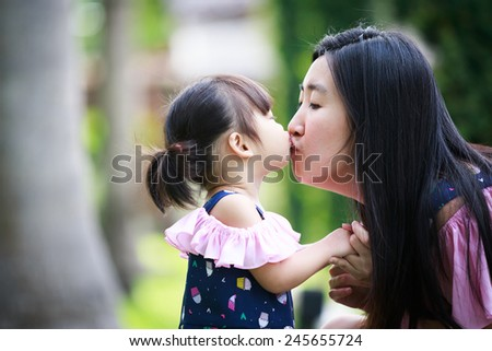 mother and daughter kiss in the garden - stock photo