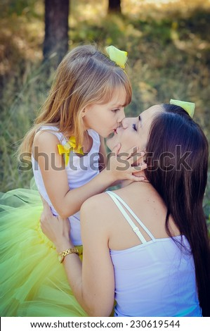 Mother and daughter kissing  in the park - stock photo