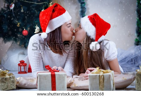 Mother and daughter kissing under Christmas tree
