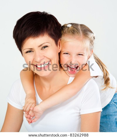 Mother and daughter laughing and looking at camera