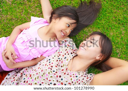 Mother and daughter laying on the green grass - stock photo