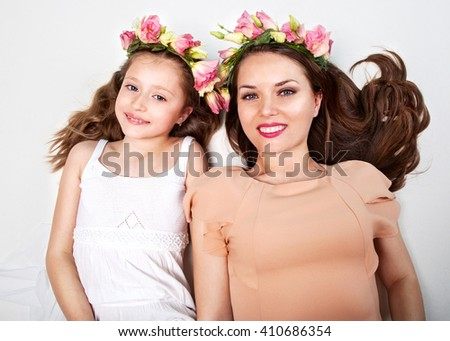 mother and daughter lie on a white background in beautiful jars of flowers and smiling. Mothers Day - stock photo