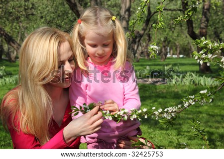 Mother and daughter look at blossoming branch of apple-tree in garden