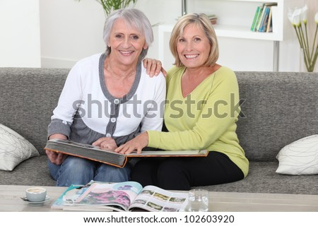 Mother and daughter looking at a picture album together - stock photo