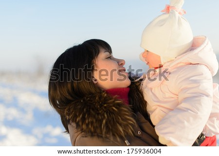 mother and daughter looking at each other - stock photo