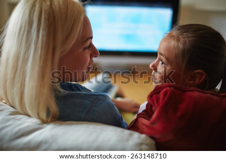 Mother and daughter looking at each other and this glance pointing at their love - stock photo