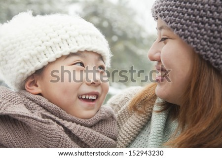 Mother and daughter looking at each other in winter