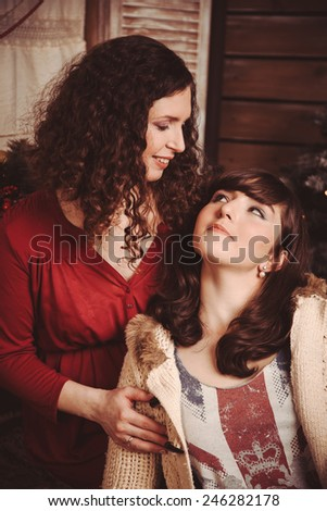 Mother and daughter looking at each other rustic Christmas Interior - stock photo