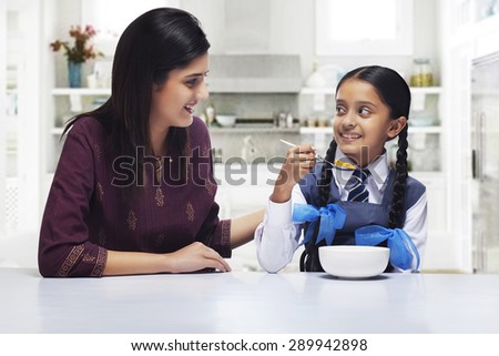 Mother and daughter looking at each other while girl having breakfast - stock photo