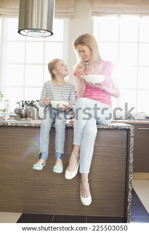 Mother and daughter looking at each other while having breakfast in kitchen - stock photo