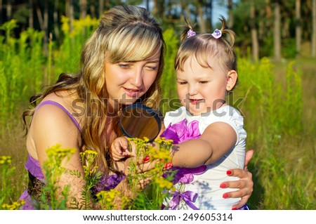 Mother and daughter looking at flowers - stock photo