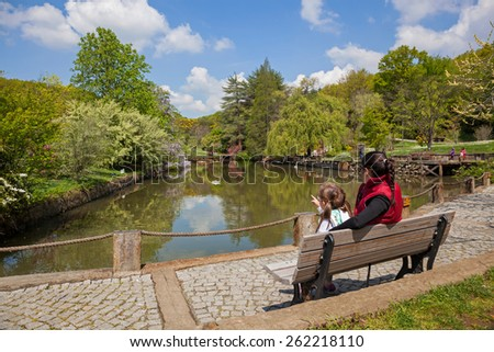 Mother and daughter looking at the lake - stock photo