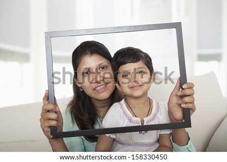 Mother and daughter looking through a picture frame  - stock photo
