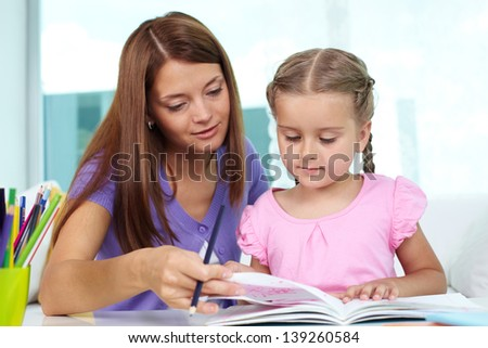 Mother and daughter looking through drawings at home - stock photo
