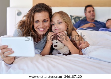 Mother and daughter lying on a bed at home together, using a digital tablet taking selfie