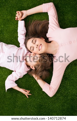 Mother and daughter lying on a green grass-like carpet together. - stock photo