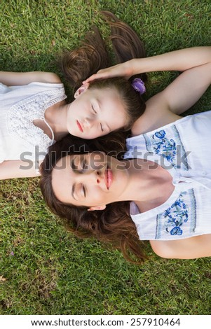 Mother and daughter lying on grass outside in the garden - stock photo