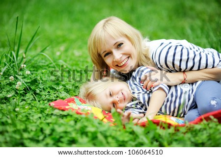 Mother and daughter lying together on grass and having fun