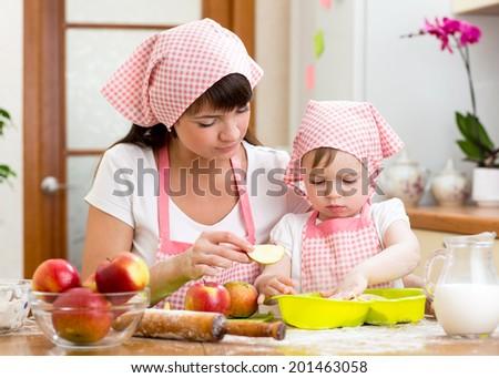 Mother and daughter making apple pie together - stock photo
