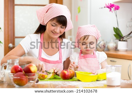 Mother and daughter making apple pie together