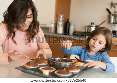 Mother and daughter making cupcakes in kitchen - stock photo