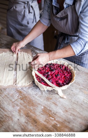 Mother and daughter making Delicious Cherry Pie, wooden table, depth of field