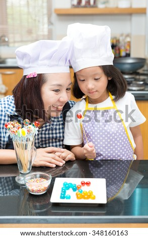 Mother and daughter making jelly ball in the kitchen