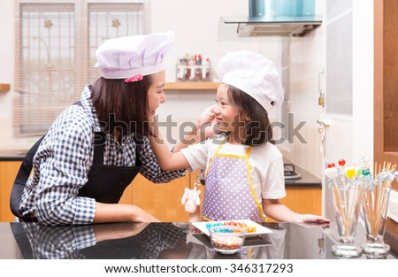 Mother and daughter making jelly candy in the kitchen