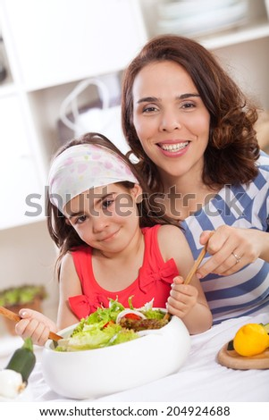 Mother and daughter making salad in kitchen - stock photo