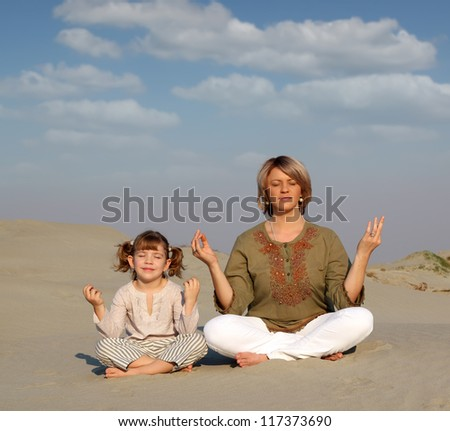 mother and daughter meditating in desert family healthy lifestyle - stock photo