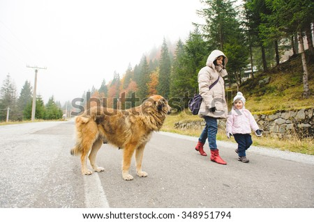 mother and daughter meeting dog on road - stock photo