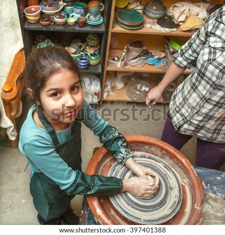 mother and daughter mold with clay, pottery children  - stock photo