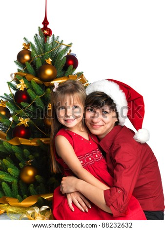 Mother and daughter near the Christmas tree - stock photo