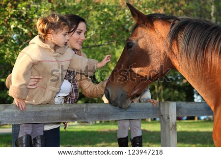 Mother and daughter next to horse - stock photo