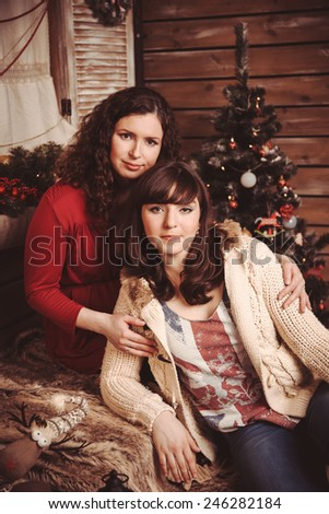 Mother and daughter on a background of the village Christmas Interior - stock photo