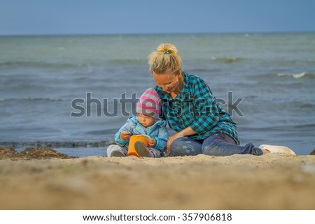 Mother And Daughter On Holiday Standing On Winter Beach - stock photo