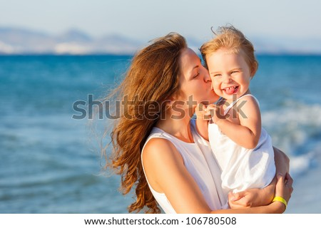 Mother and daughter on the beach - stock photo