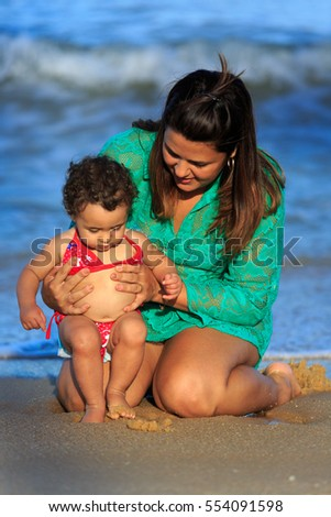 Mother and daughter on the beach playing