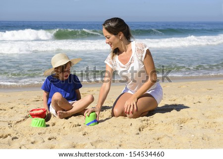 Mother and daughter on the beach playingin the sand - stock photo