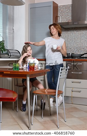 mother and daughter on the kitchen behind the table drinking beverage and eating sweets - stock photo