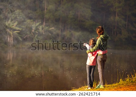 Mother and daughter on the lake, Shot is taken from behind - stock photo