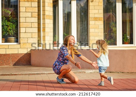 Mother and daughter on the walk in the city park. Daughter runs to her mother. - stock photo