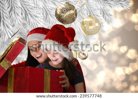 Mother and daughter opening gift against christmas decorations on branch - stock photo