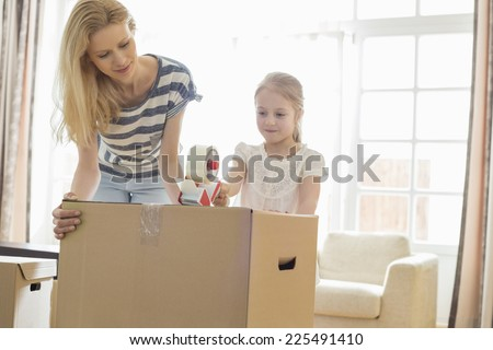 Mother and daughter packing cardboard box at home - stock photo