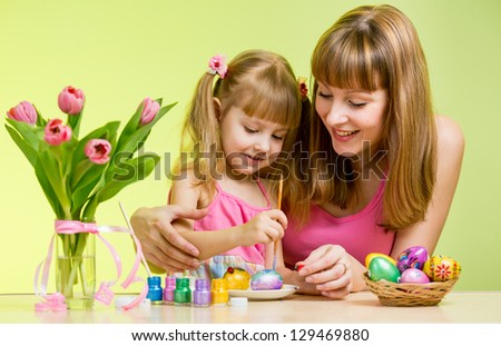 mother and daughter paint easter eggs - stock photo