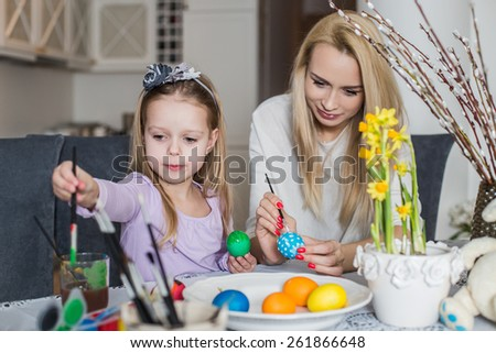 Mother And Daughter Painting Easter Eggs In Home. Girl with her mother learning to paint Easter eggs. Cozy home atmosphere. Easter - stock photo