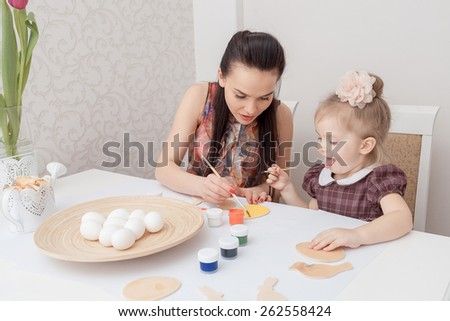 Mother and daughter painting Easter holiday eggs